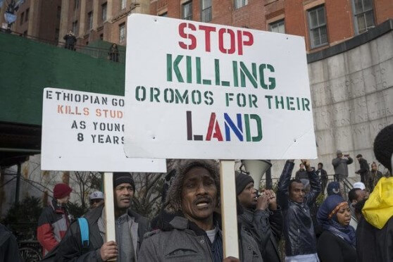 "MANHATTAN, NEW YORK, NY, UNITED STATES - 2016/01/15: A demonstrator holds a sign while demonstrating opposite United Nations Headquarters. Several hundred Ethiopian-American demonstrators from around the U.S. gathered opposite United Nations Headquarters in New York City to express their anger over the recent deaths of over 140 protesters in Ethiopia at the hands of government security forces sent to contain the protests over the Addis Abba ""master plan."". (Photo by Albin Lohr-Jones/Pacific Press/LightRocket via Getty Images)"
